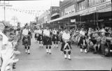 A bagpipe band marching along Victoria Street.